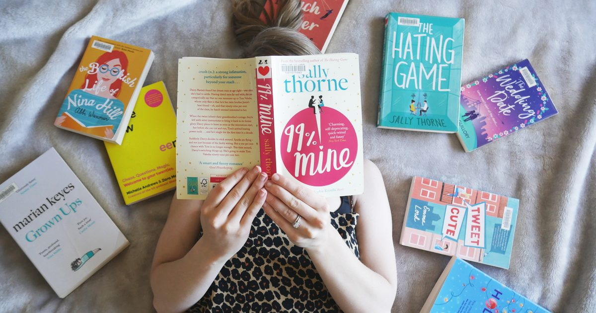 woman laying on bed with lots of fiction books