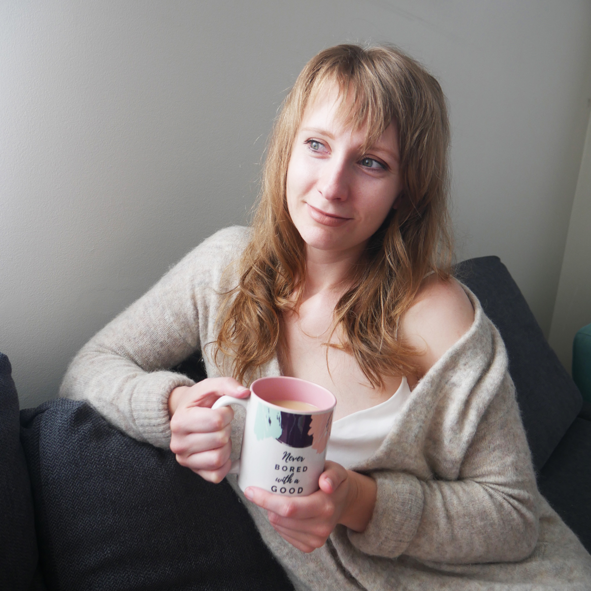 woman sitting on lounge with cup of tea