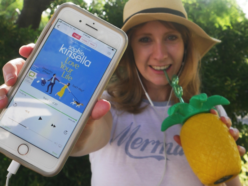 woman holding phone with sophie kinsella audiobook and pineapple drink
